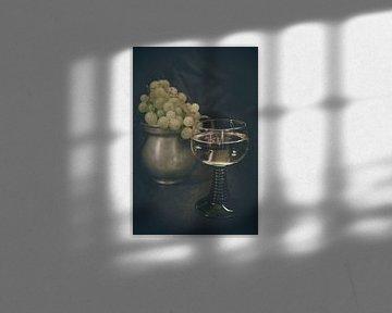 Een glas witte wijn in een Romeins glas met een metalen werper met lichte druiven op de achtergrond van Edith Albuschat