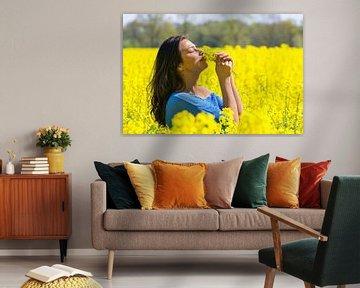 Frau riecht Blumen auf dem gelben Rapssamengebiet von Ben Schonewille