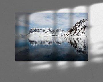 Diep in het fjord is het water rustig en reflecteert het landschap