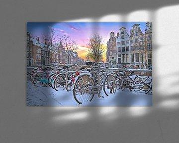 Besneeuwd Amsterdam in Nederland bij zonsondergang von Nisangha Masselink