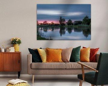 Zonsondergang in Emmen met spiegeling in de grote rietplas van Kim Bellen