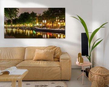 Gracht in de oude binnenstad van Amsterdam bij nacht van Werner Dieterich