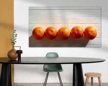 Vijf sinaasappels op een rij op een witte houten tafel van Maarten Pietersma
