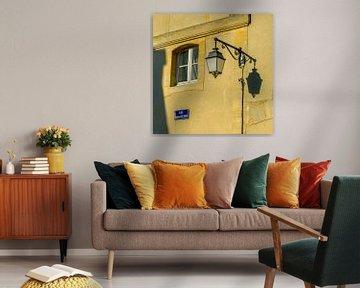 Oude lantaarn met zijn schaduw tegen warme gele muur von Petra Cremers