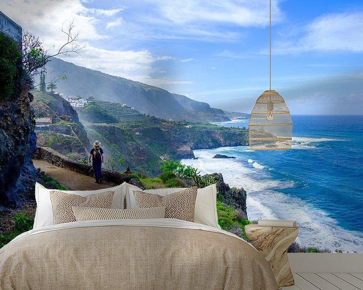 Sfeerimpressie behang: Wandelaar loopt over een pad met uitzicht over zee en kliffen. van Lidewij Olive