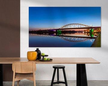 Die Arnheimer John-Frostbrücke am Abend über einem flachen Rhein