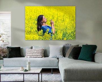 Jonge Columbiaanse vrouw ruikt gele bloemen in koolzaadveld van Ben Schonewille