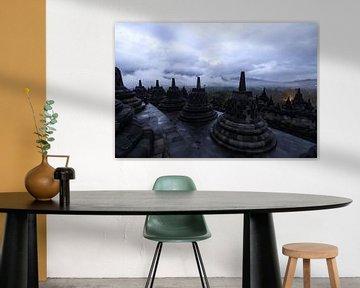 Sfeervolle plaat van de Borobudur voor zonsopkomst op een dag met zware bewolking en neerslag