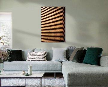 Muster einer Jalousie im Sonnenlicht auf einer Holzoberfläche