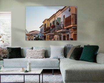 een rij woningen aan elkaar in verschillende kleuren met balkons