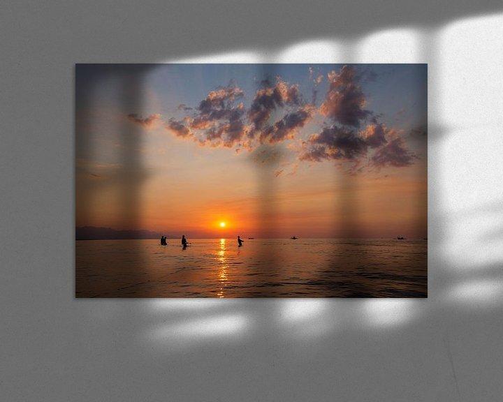 Sfeerimpressie: De vissers silhouetteren op het strand bij kleurrijke zonsondergang in Bali, Indonesië van Tjeerd Kruse