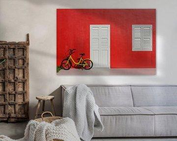 Rode muur met gele kinderfiets