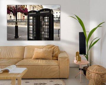 Schwarze Telefonzellen London neben hängenden Blumen von Mireille Schipper