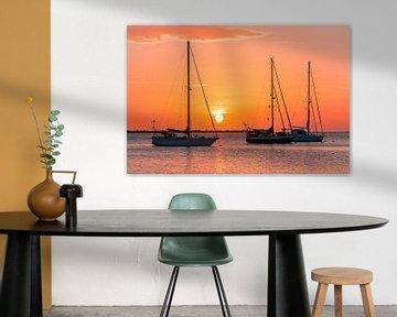 Oranje zonsondergang met zeilboten aan de kust op zee van Ben Schonewille