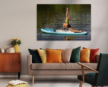 Junge Frau beim Yoga auf SUP oder Paddelbrett auf dem Wasser in der Natur. von Ben Schonewille