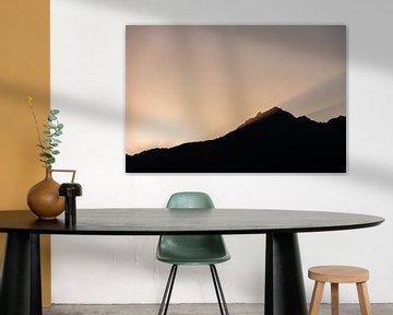 Bergtop silhouet in warm tegenlicht (avondzon) van Hidde Hageman
