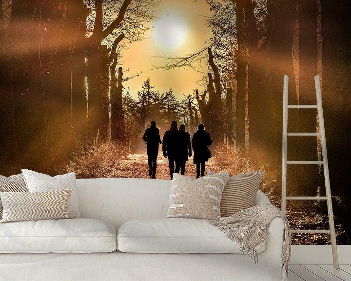 Sfeerimpressie behang: Wandelaars in het bos met de zon in het tegenlicht van Harrie Muis