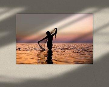 Nackte Frau mit einem Fischernetz bei Sonnenuntergang im Wattenmeer von Arjan Groot