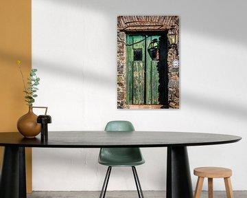 Oude groene houten deur met lantaarn aan de muur