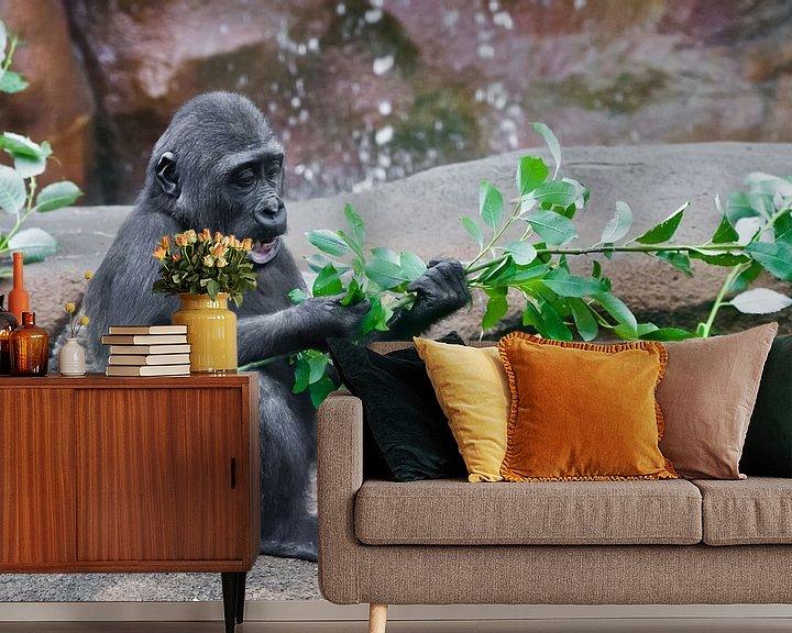 Beispiel fototapete: süßes kleines Affenbaby frisst grüne Blätter, wenn es auf den Felsen bei den Felsen sitzt von Michael Semenov