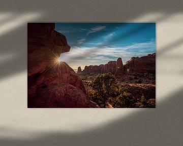De zonsondergang met lens flare in Arches National Park van Maarten Oerlemans
