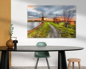 Windmolen in Nederlands landschap tijdens zonsondergang in Abcoude