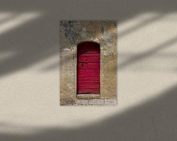 Auffällige, rustikale, rote Tür in einer verwitterten, verputzten Wand von Wil Wijnen