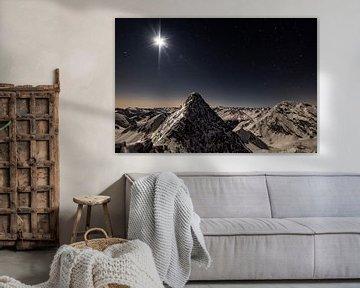 Bergtoppen in het maanlicht onder een sterrenhemel