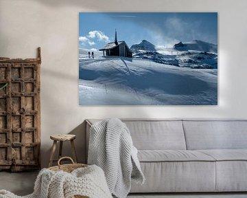 Wanderer an einer Kapelle in einer winterlichen Berglandschaft. von Ralph Rozema