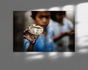 Un enfant avec un crabe dans un village de pêcheurs aux Philippines sur Yvette Baur