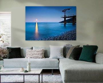 Sonnenuntergang über dem Meer, ein kleiner Kran auf der Mole, surfen auf dem Mondpfad. von Michael Semenov