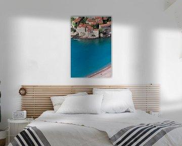oude huizen met een helderblauwe zee en een verlaten zandstrand met één persoon. perfecte vakantie.  van Michael Semenov