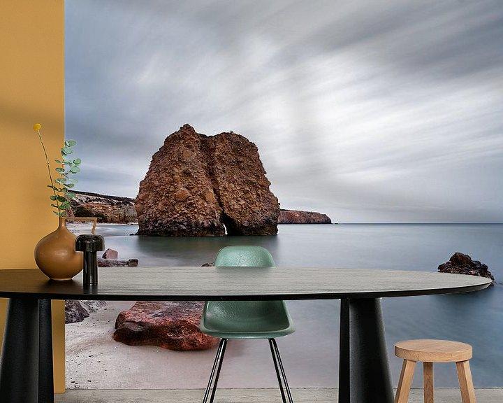 Sfeerimpressie behang: Strand met roodachtige steenblokken, water en wolkenbeweging van Ralf Lehmann
