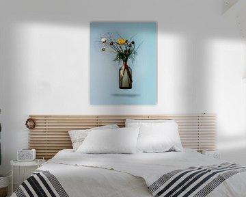 Boeket bloeiende bloemen in zwevende vaas tegen blauwe achtergrond