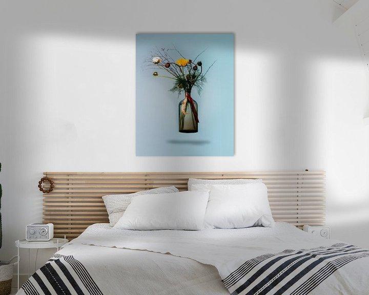 Sfeerimpressie: Boeket bloeiende bloemen in zwevende vaas tegen blauwe achtergrond van Atelier Liesjes