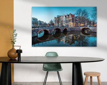 De prachtige Amsterdamse grachten tijden het blauwe uurtje. van Claudio Duarte