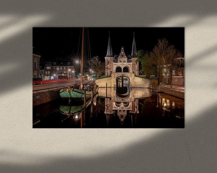 Sfeerimpressie: Spiegelend Sneker skûtsje en waterpoort in stadsgracht van Sneek van Fotografiecor .nl