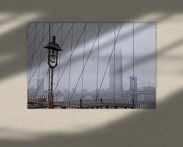 Mistig uitzicht vanaf The Brooklyn Bridge in New York van Marieke van de Velde