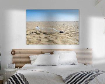 Ein Altglas Weinflasche am Sandstrand in der Sonne, Konzept der Meeresverschmutzung von Leoniek van der Vliet