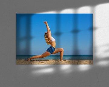 Jonge Nederlandse vrouw in zomerkleding oefent yoga op strand van Hurghada in Egypte van Ben Schonewille