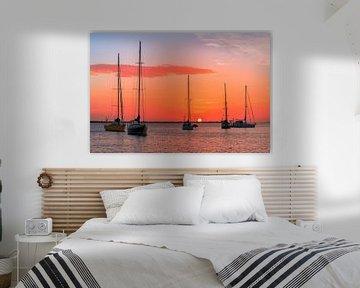Groep zeilbootjes op zee met oranje ondergaande zon van Ben Schonewille