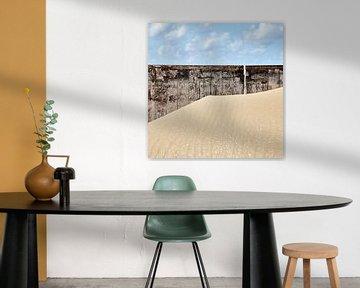 Zandverstuiving tegen een houten muur op het strand van Hans Kwaspen