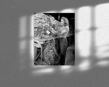Frau überprüft technische Installation und Kontrolltafel bei Boeing 1942