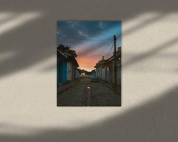 Orangefarbener Sonnenaufgang in einer Straße in Trinidad de Cuba mit Oldtimer und Kater von Michiel Dros