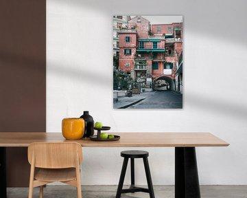 Rood Italiaans appartementengebouw met een de straat eronderdoor in Amalfi