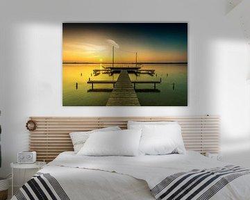 Steg mit Segelboot im Sonnenuntergang
