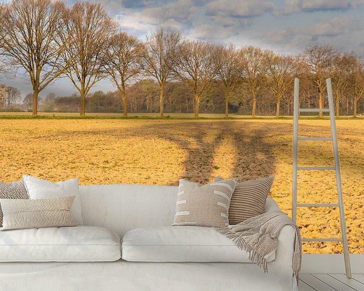 Sfeerimpressie behang: Langwerpige schaduw van bomen over het akkerland-in kleur van Karin de Jonge