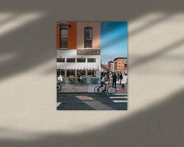 Straßenecke mit orangefarbenem Gebäude, Restaurant und Radfahrer in Manhattan, New York von Michiel Dros