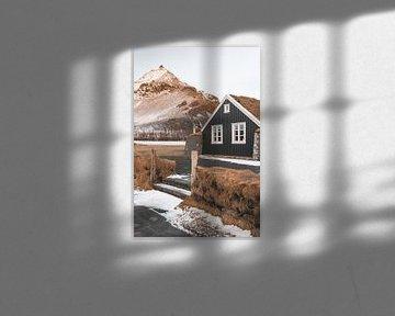 Houten huis met gras op het dak bij zonsopkomst in Arnarstapi, Ijsland