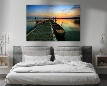 Jetée avec bateau à rames au coucher du soleil